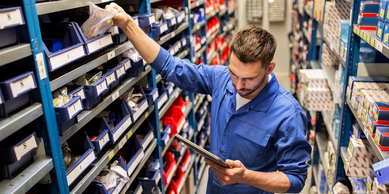 Warehouse worker picking consumer goods from a shelf bin.